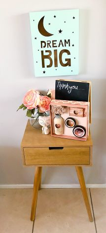 Small wooden table with pink bunch of flowers in glass vase, small cream felt owl, little black board with thank you written on it and box filled with beauty products sitting on top against cream wall with mint sign on the wall that says dream big