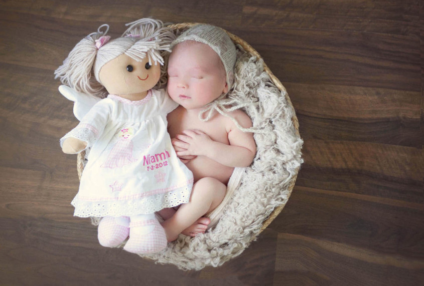 Newborn baby boy in basket with cream bonnet cuddling rag doll belonging to sibling who has died