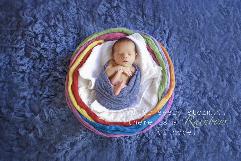 Newborn baby boy sleeping wrapped in blue blanket laying on white cloud wrapped in rainbow on blue fur