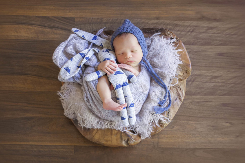 Newborn baby boy sleeping wrapped in grey laying on grey blanket in wooden log prop cuddling blue and grey rabbit and wearing blue bonnet laying on wooden floors