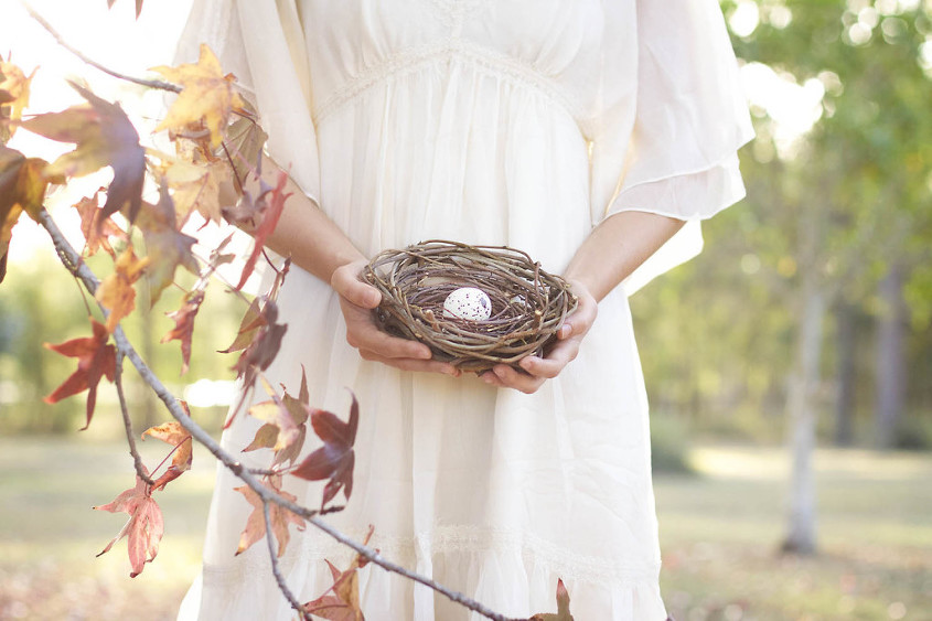 Woman in cream dress standing beside autum leaves on a tree holding nest with egg