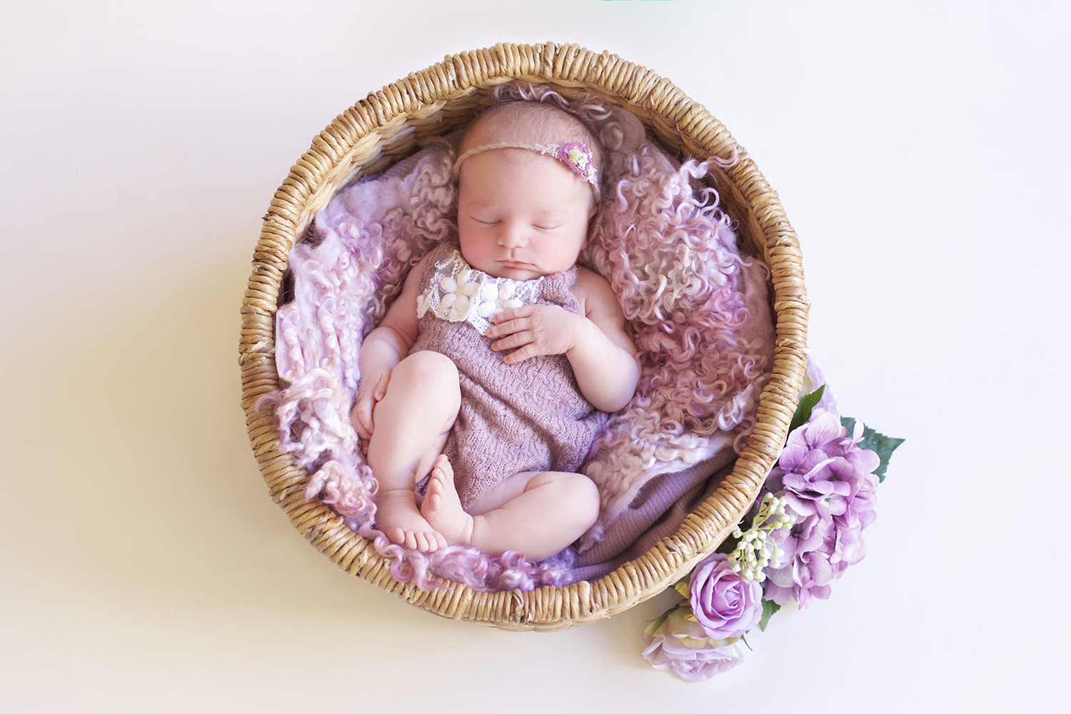 Newborn baby girl wearing pink romper sleeping in round cane basket with pink curly felt with pink flowers