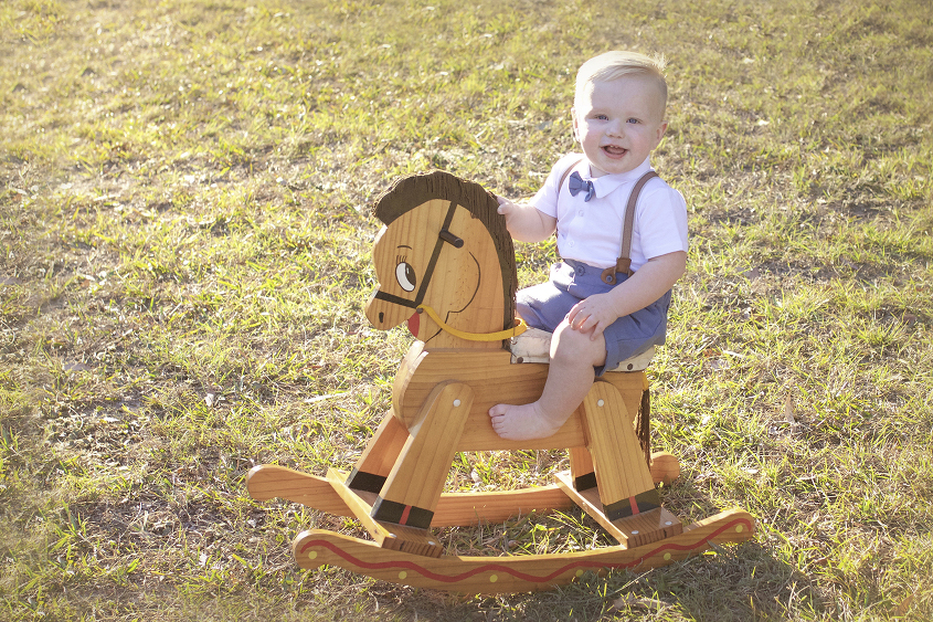 One year old boy wearing white button up shirt, grey shorts, braces and bow tie in park at sunset on wooden rocking horse