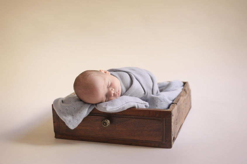 Newborn baby boy sleeping in wooden drawer with blue wrap and blanket and pillow on cream backdrop