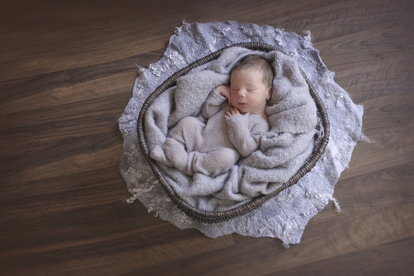 Newborn baby boy in oval black cane basket with grey curly felt and blanket wearing grey romper on wooden floor