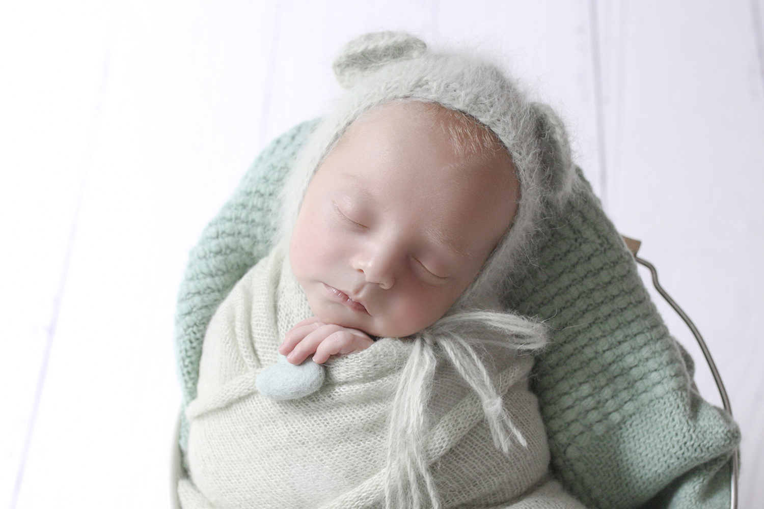 Newborn baby boy sleeping in cream iron bucket with mint wrap and blanket and knit bear bonnet on white wooden floor