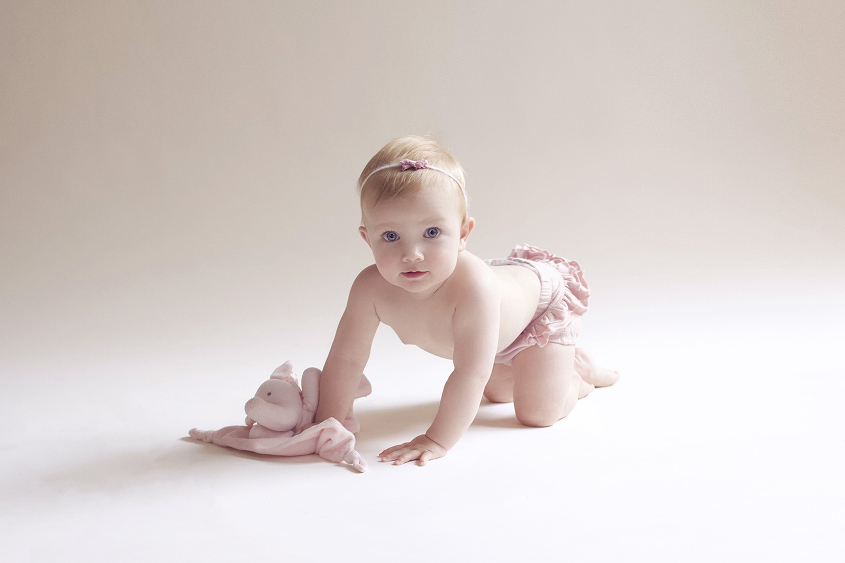 One year old crawling on cream floor wearing pink romper and pink bow tieback and holding pink soft elephant toy