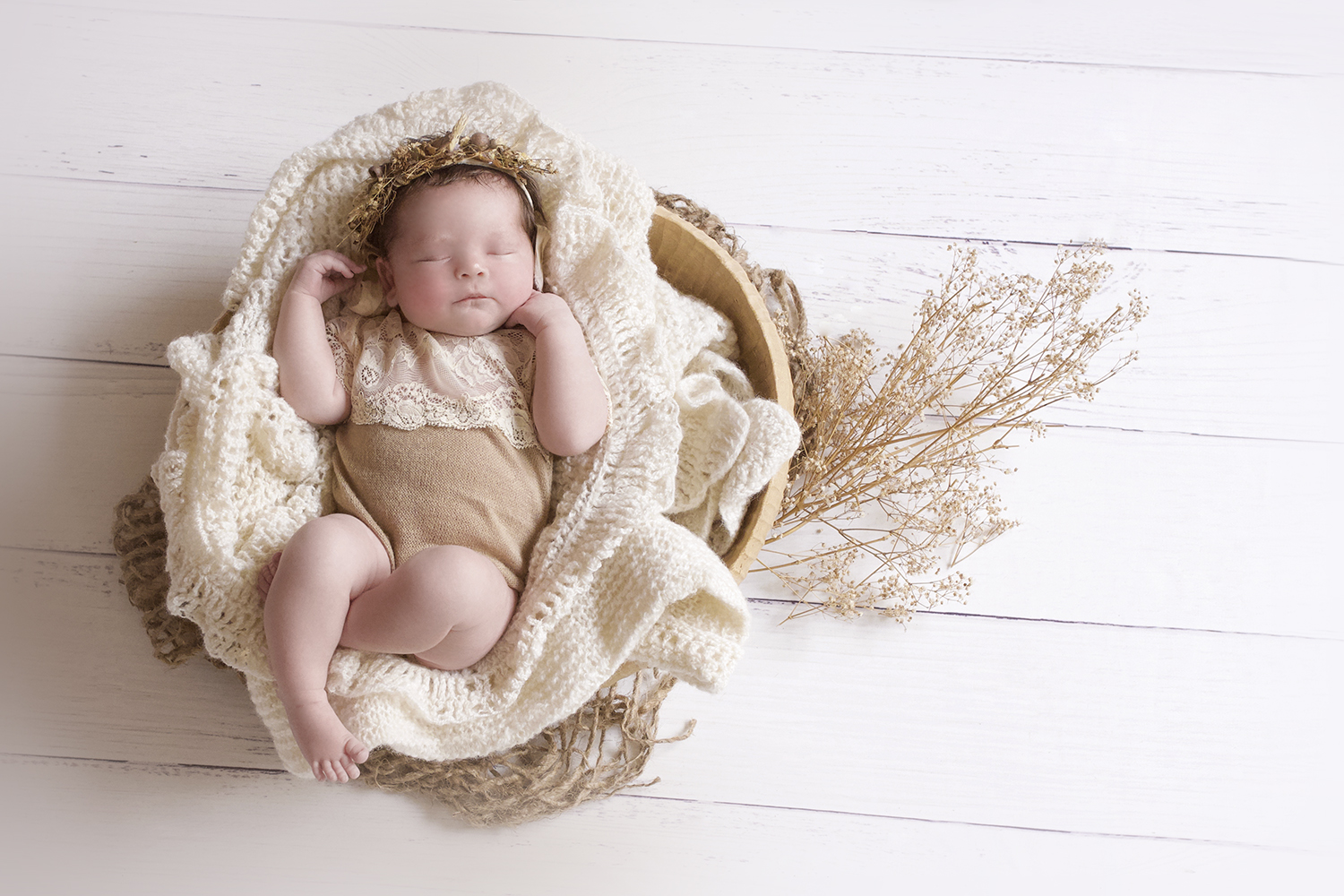 Newborn baby girl sleeping in oval wooden bowl with cream knit blankets jute layer and dried flowers with baby wearing brown and cream lace romper and brown dried flower and gumnut headband