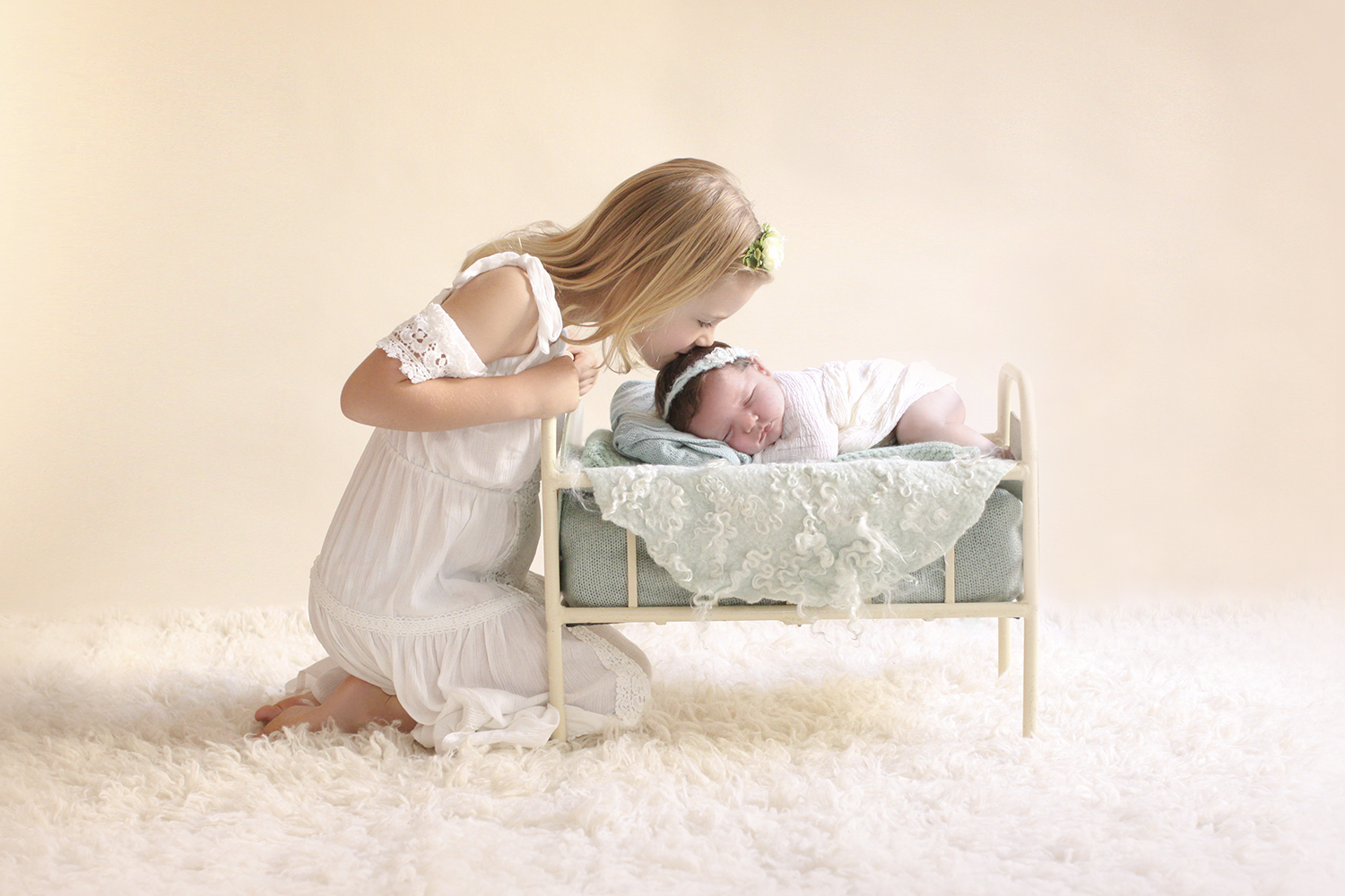 Newborn baby girl wrapped in cream wrap sleeping on cream vintage iron bed with mnt blanket and felt layer and tieback being kissed by big sibling sister on cream felt floor