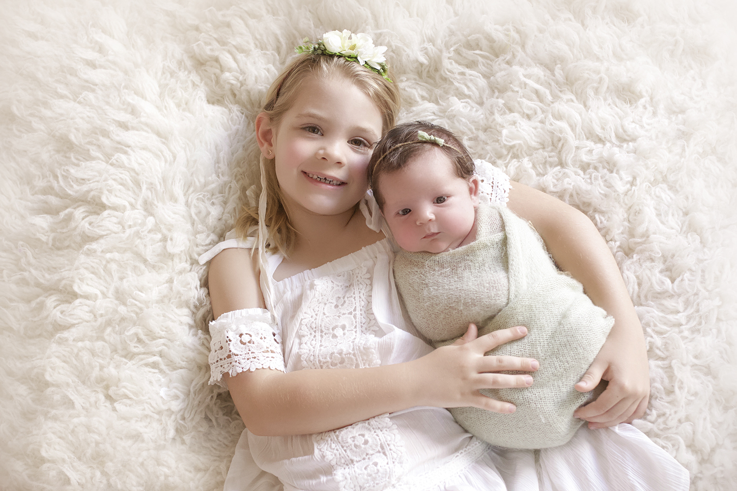 Newborn baby girl wrapped in green knit blanket with green bow tieback being held by sibling big sister wearing white lace dress and flower tieback laying on cream fur