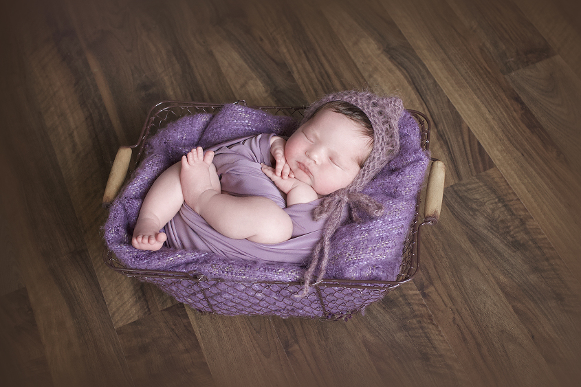 Newborn baby girl sleeping in farmers basket with purple blanket and wrap and tieback and knit bonnet