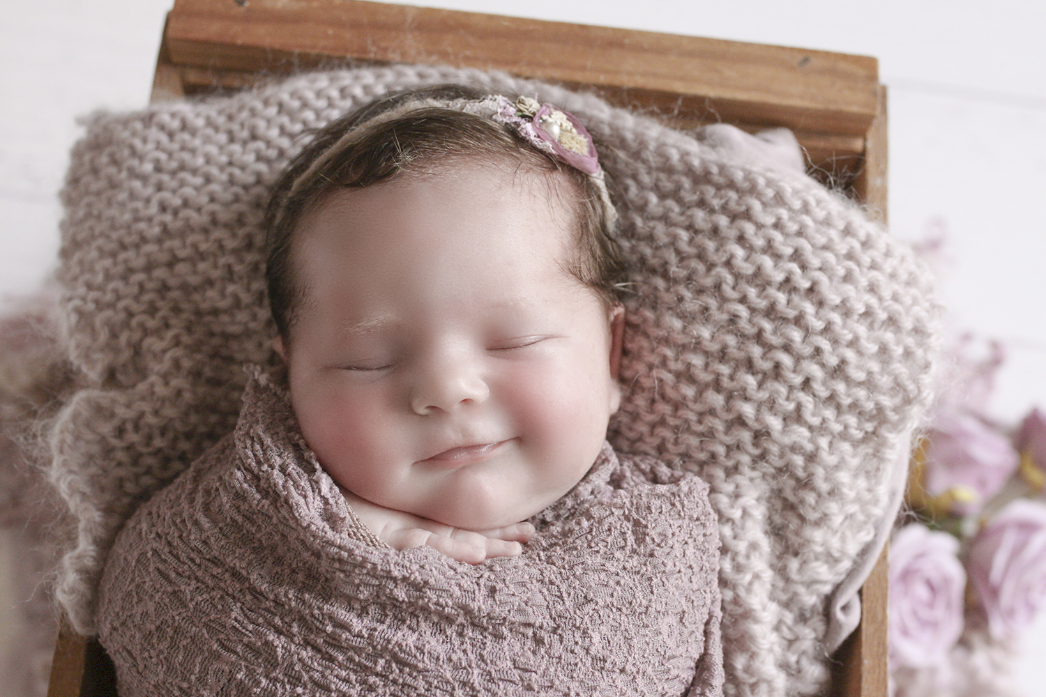 Newborn baby girl sleeping in wooden crate with purple blanket and wrap and knit layer and tieback