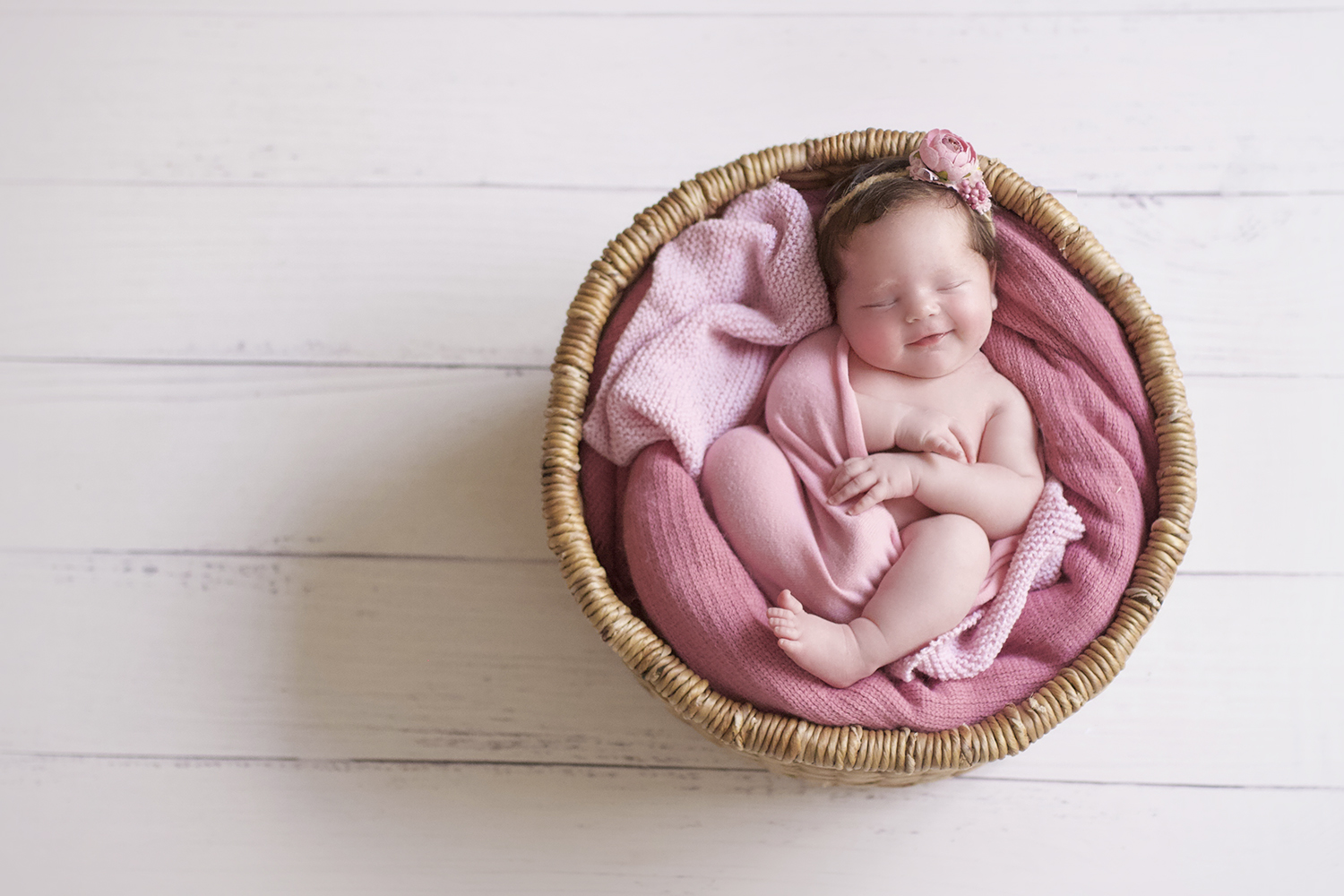 Newborn baby girl sleeping in round cane basket with pink blanket and wrap and knit layer and tieback on white wooden floor