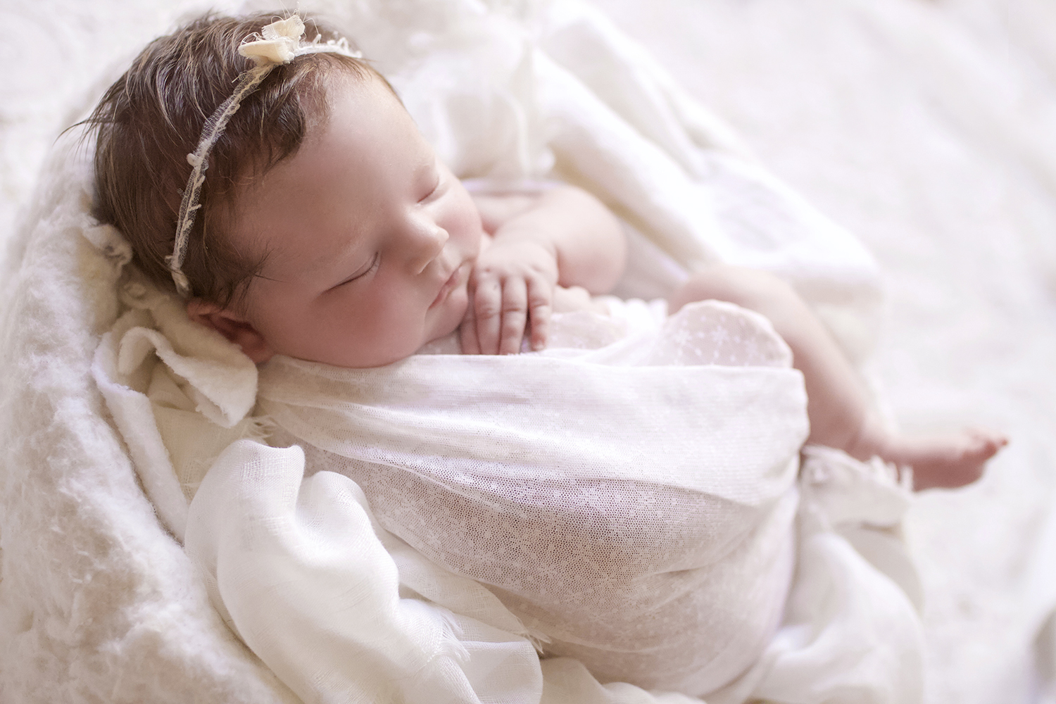 Newborn baby girl sleeping in white felt bowl with white wrap and tieback