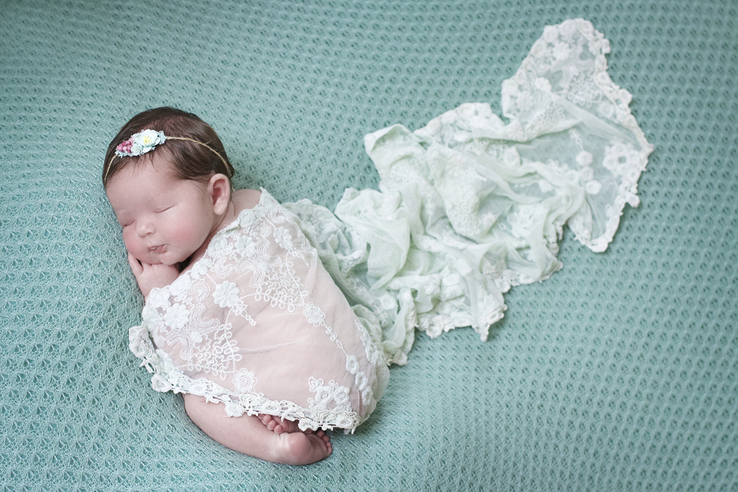 Newborn baby sleeping on teal blanket with teal flower tieback and teal lace wrap