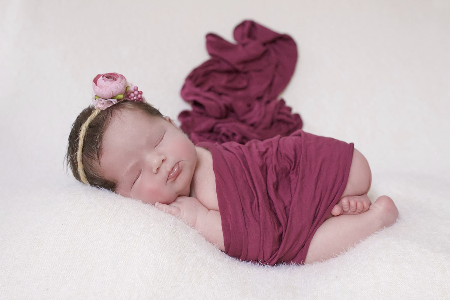 Newborn baby girl sleeping on cream blanket with plum wrap and pink flower tieback