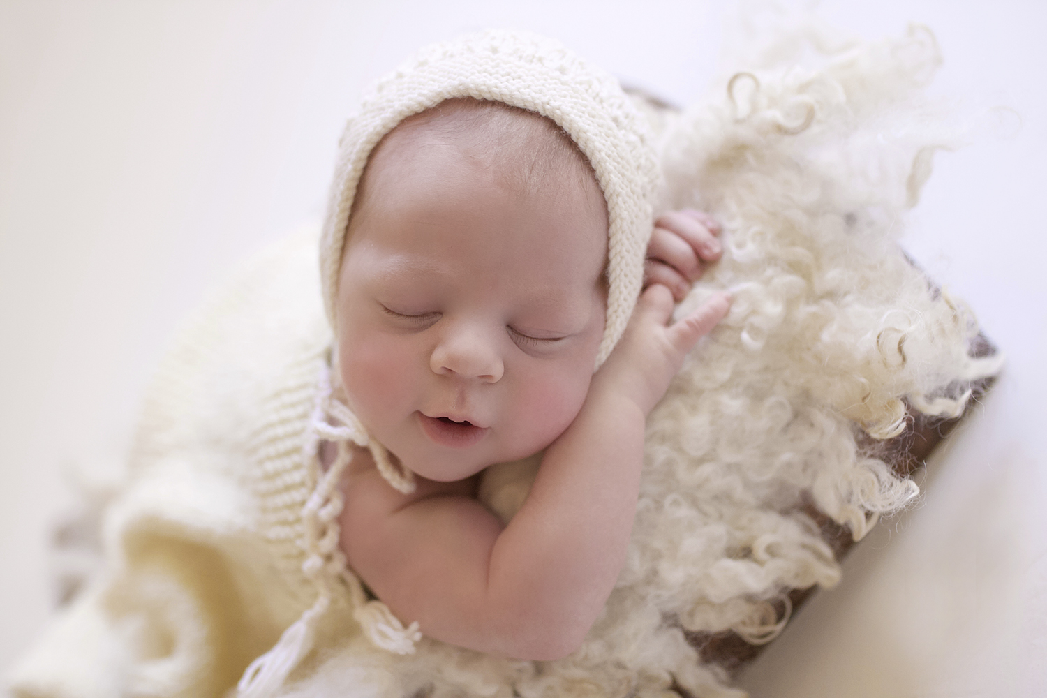 Newborn baby boy sleeping in wooden drawer with cream curly fur and knit layer and bonnet