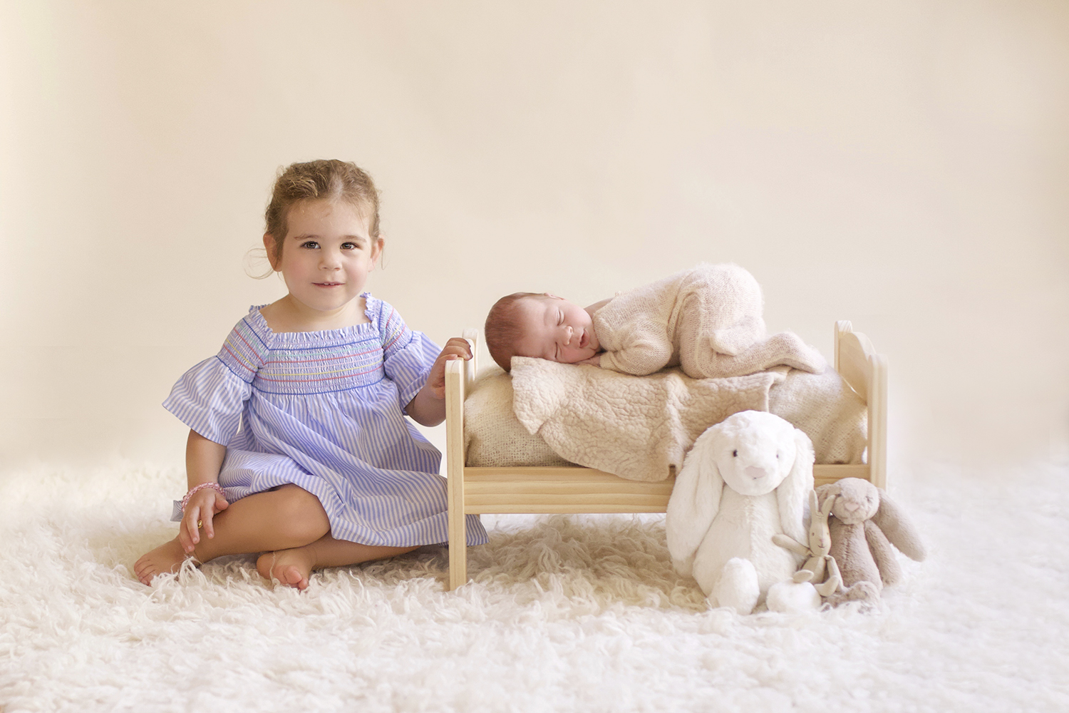 Newborn baby boy in cream romper sleeping on wooden bed with cream blankets and cream fur on the ground with soft toy bunnies and sibling big sister in blue dress