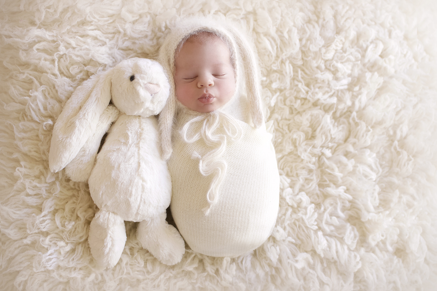 Newborn baby boy sleeping on cream fur wrapped in cream blanket with cream knit bunny bonnet and cream soft bunny toy