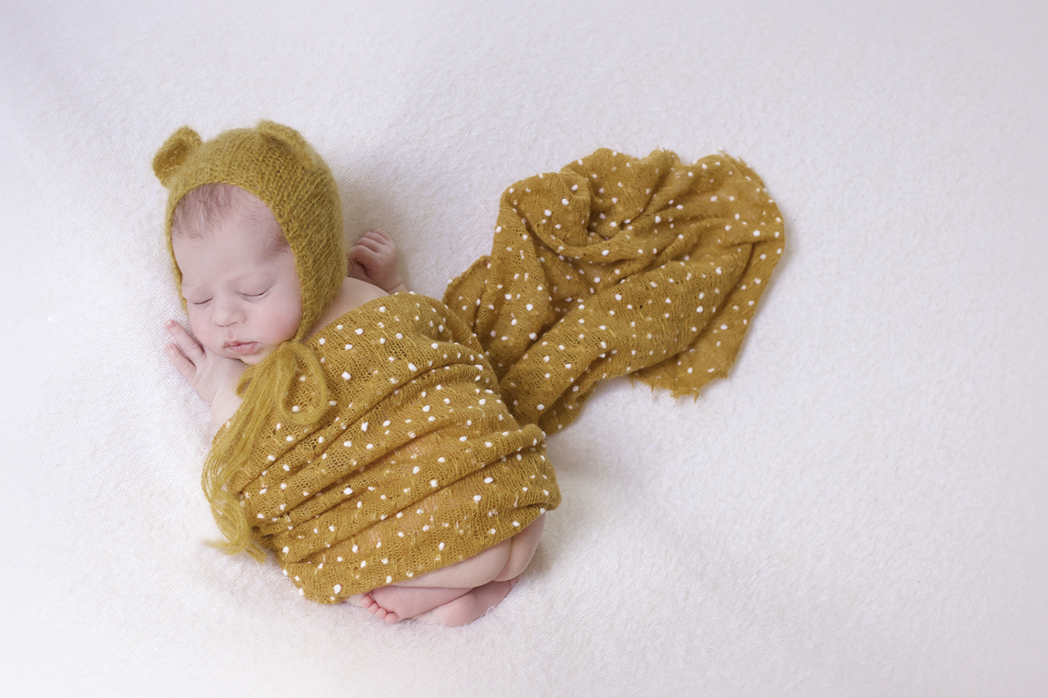 Newborn baby boy sleeping on cream blanket with mustard wrap and bear knit bonnet