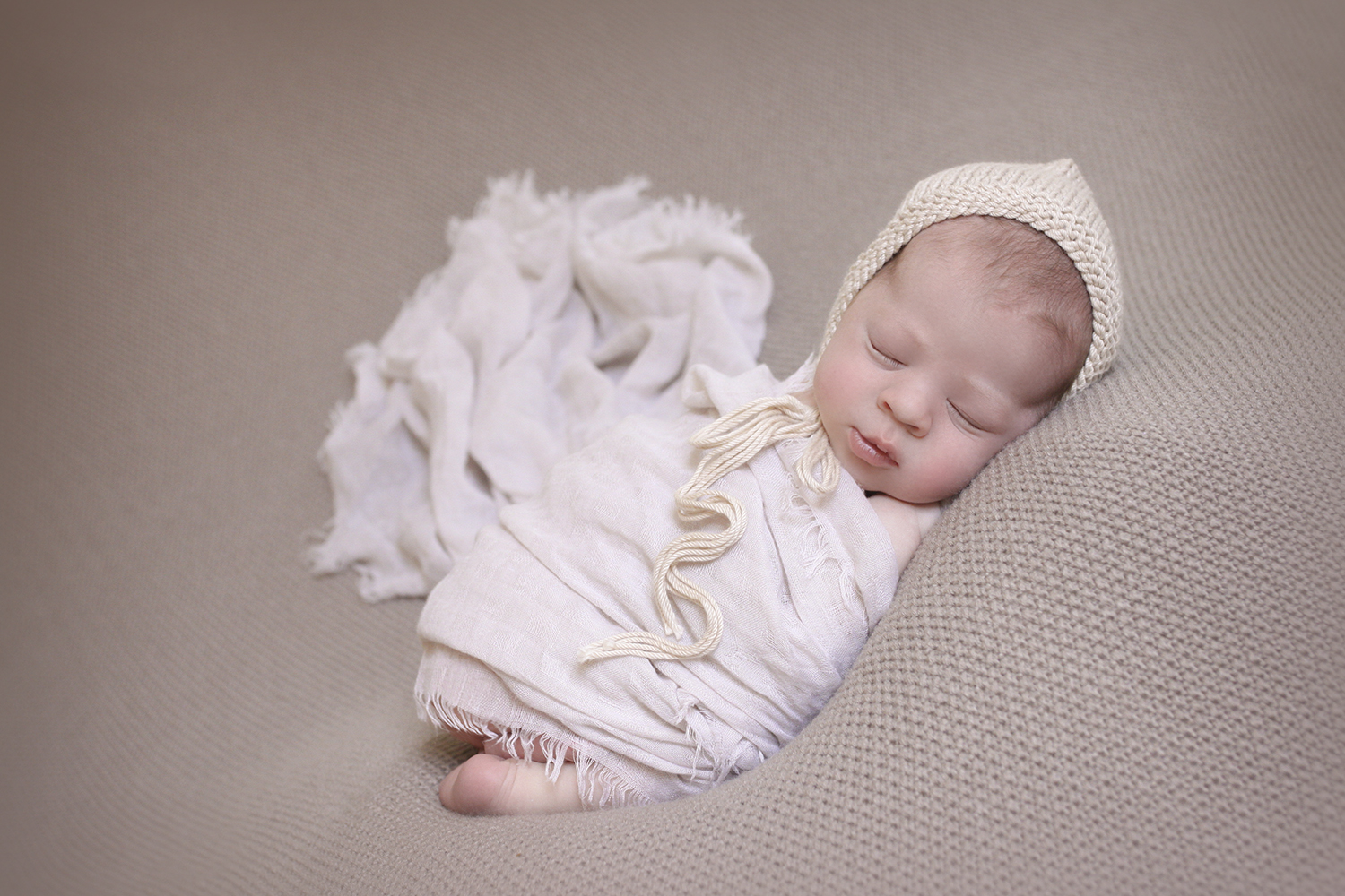 Newborn baby boy sleeping on brown blanket with tan knit bonnet and cream wrap