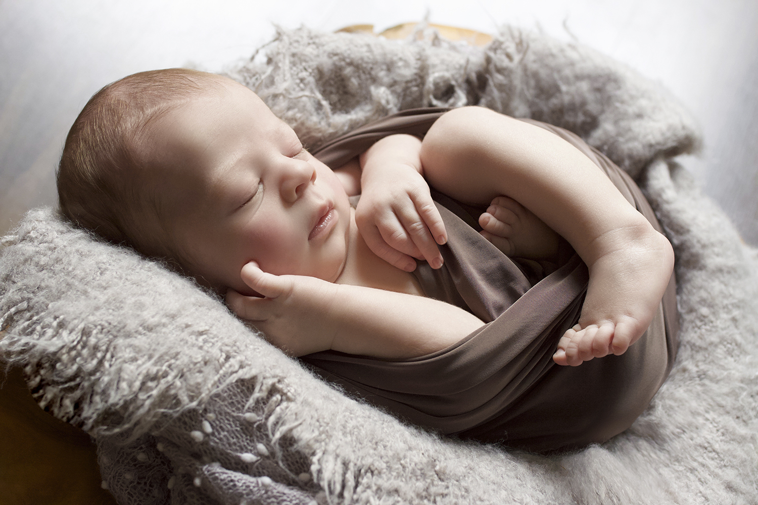 Newborn baby boy sleeping in log bowl with grey blanket and wrap and felt layer and bonnet