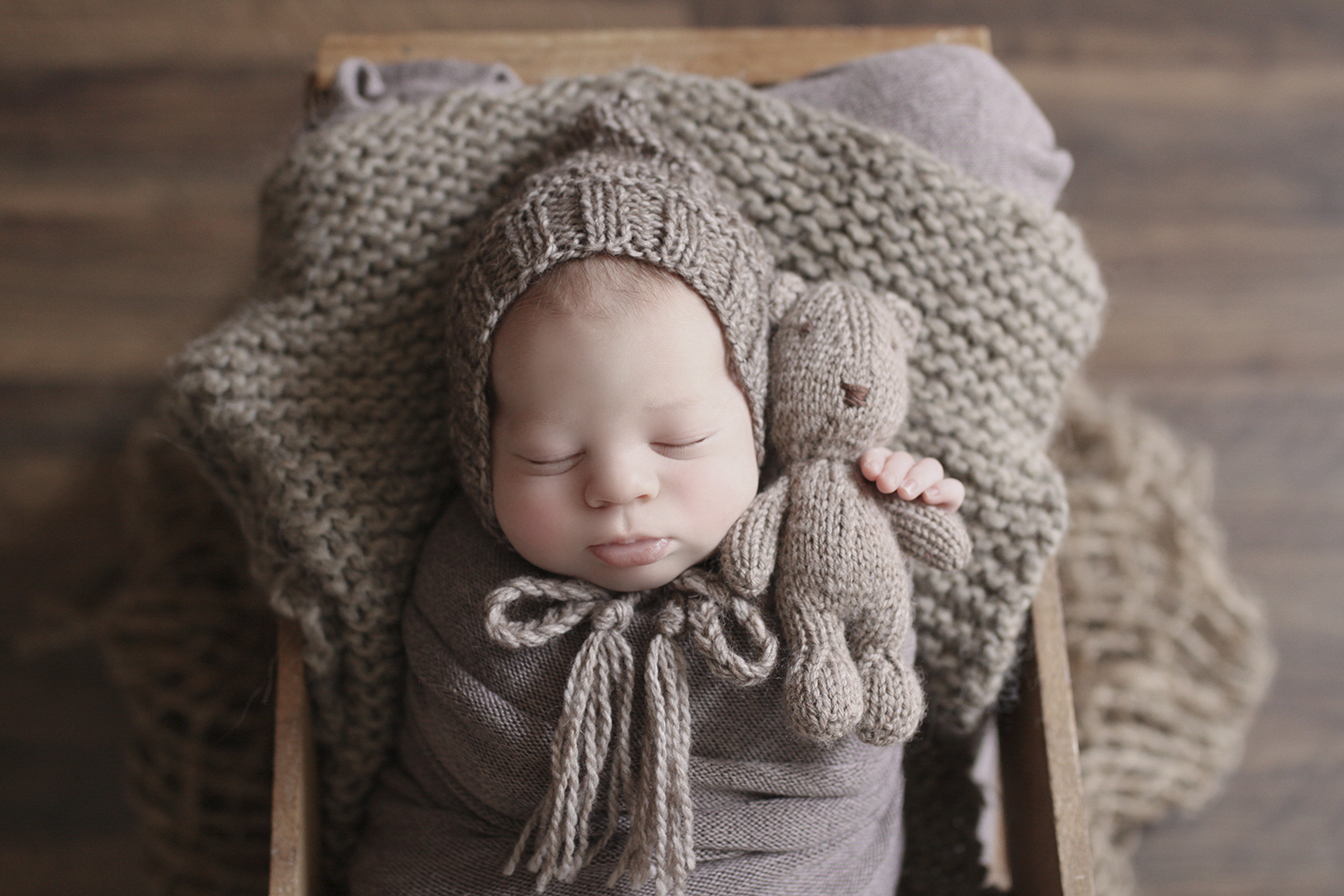 Newborn baby boy sleeping in wooden crate with brown wrap and knit layer and bonnet and bear