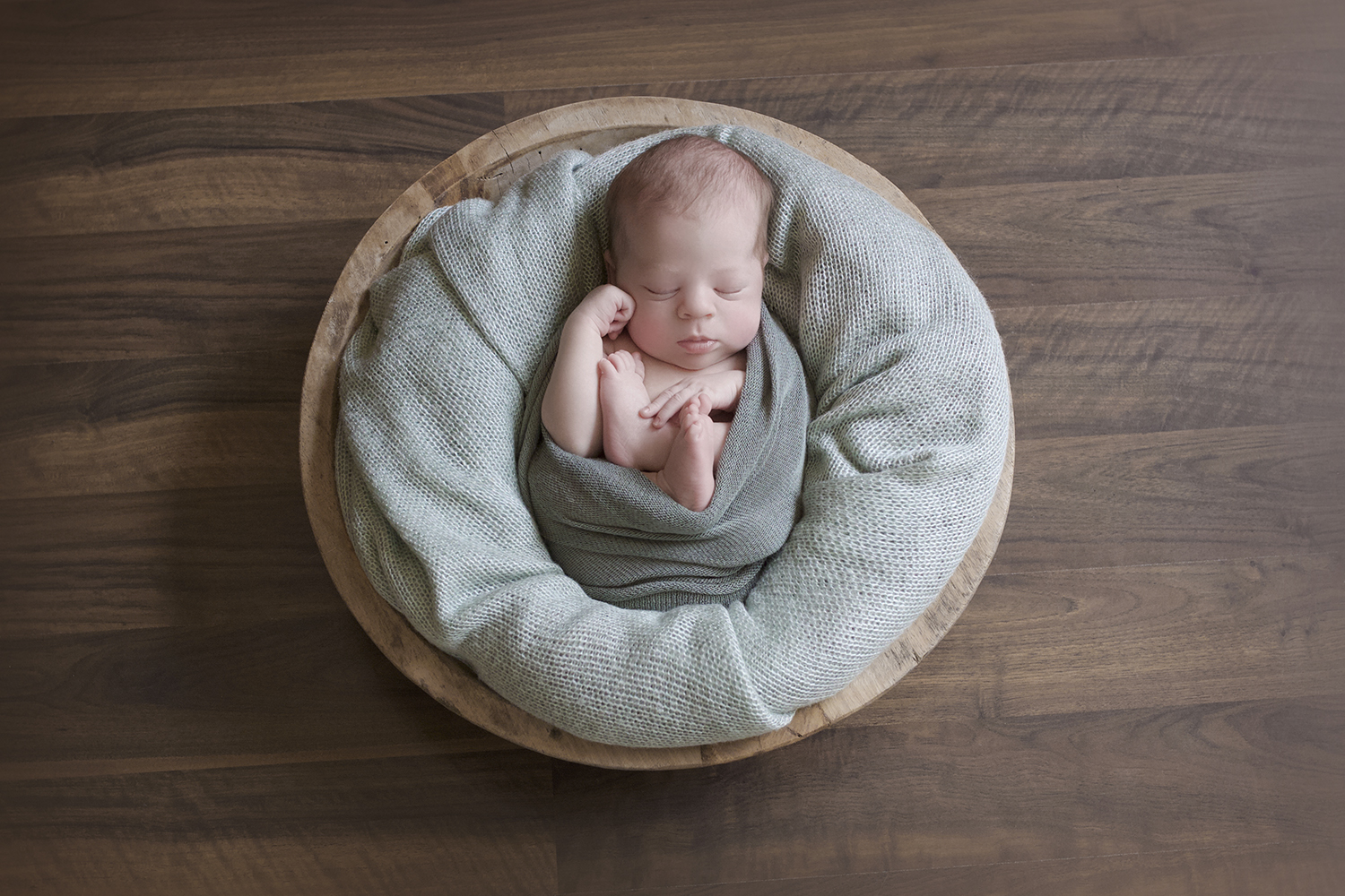 Newborn baby boy sleeping in round wooden bowl with mint blanket and wrap