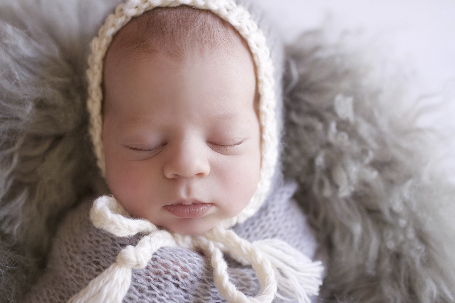 Newborn baby boy sleeping in cream bucket with grey curly fluff layer and grey knit wrap and bonnet on white wooden floor