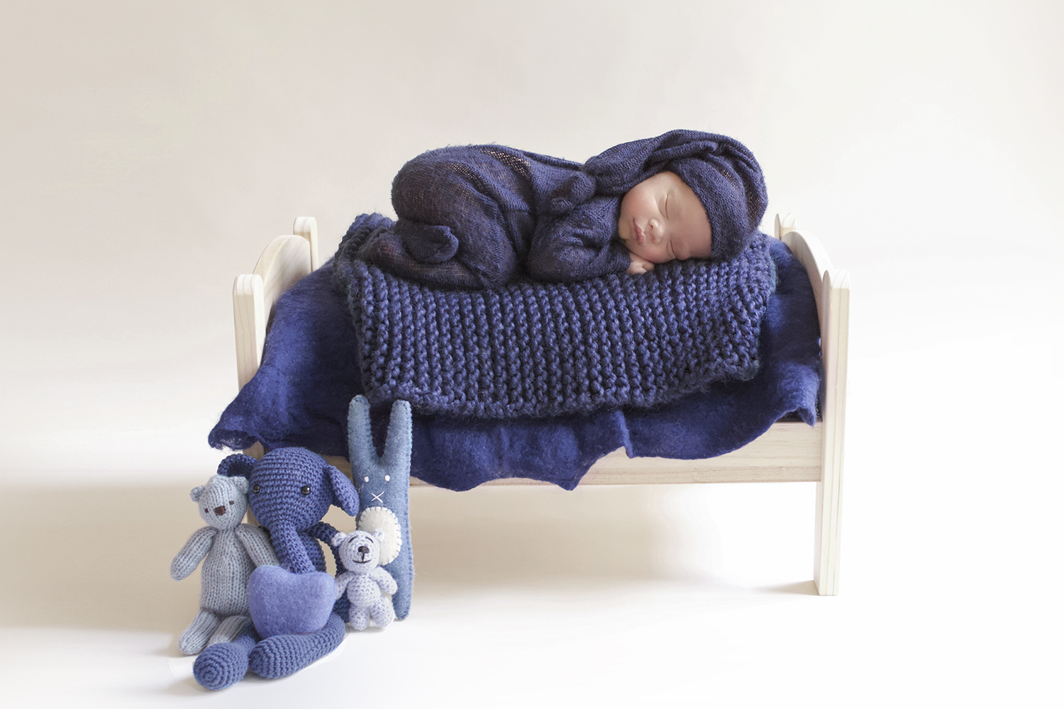 Newborn baby boy sleeping on wooden bed wearing navy knit romper and bonnet with blue blanket and knit layer and soft toys