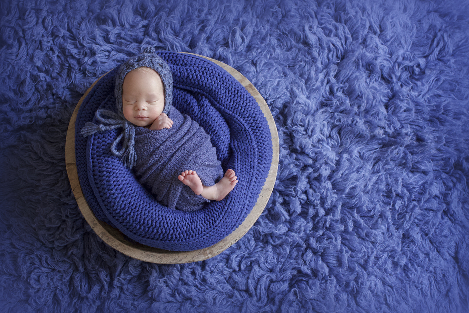 Newborn baby bpy sleeping in round wooden bowl with blue blanket and wrap and bonnet on blue fur