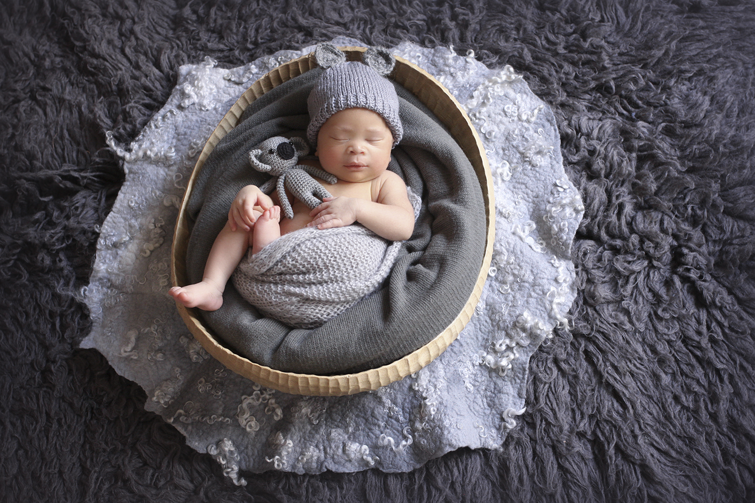 Newborn baby boy sleeping in oval wooden bowl on grey fur with grey curly felt and grey blanket and wrap and bear bonnet and knit koala toy