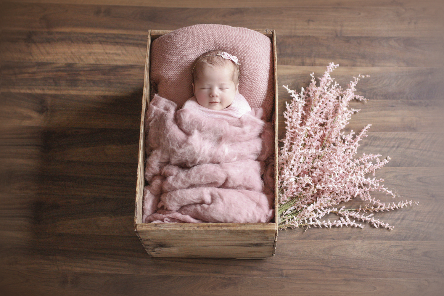Newborn baby girl sleeping in wooden crate with pink blanket and felt and wrap and flowers on wooden floor