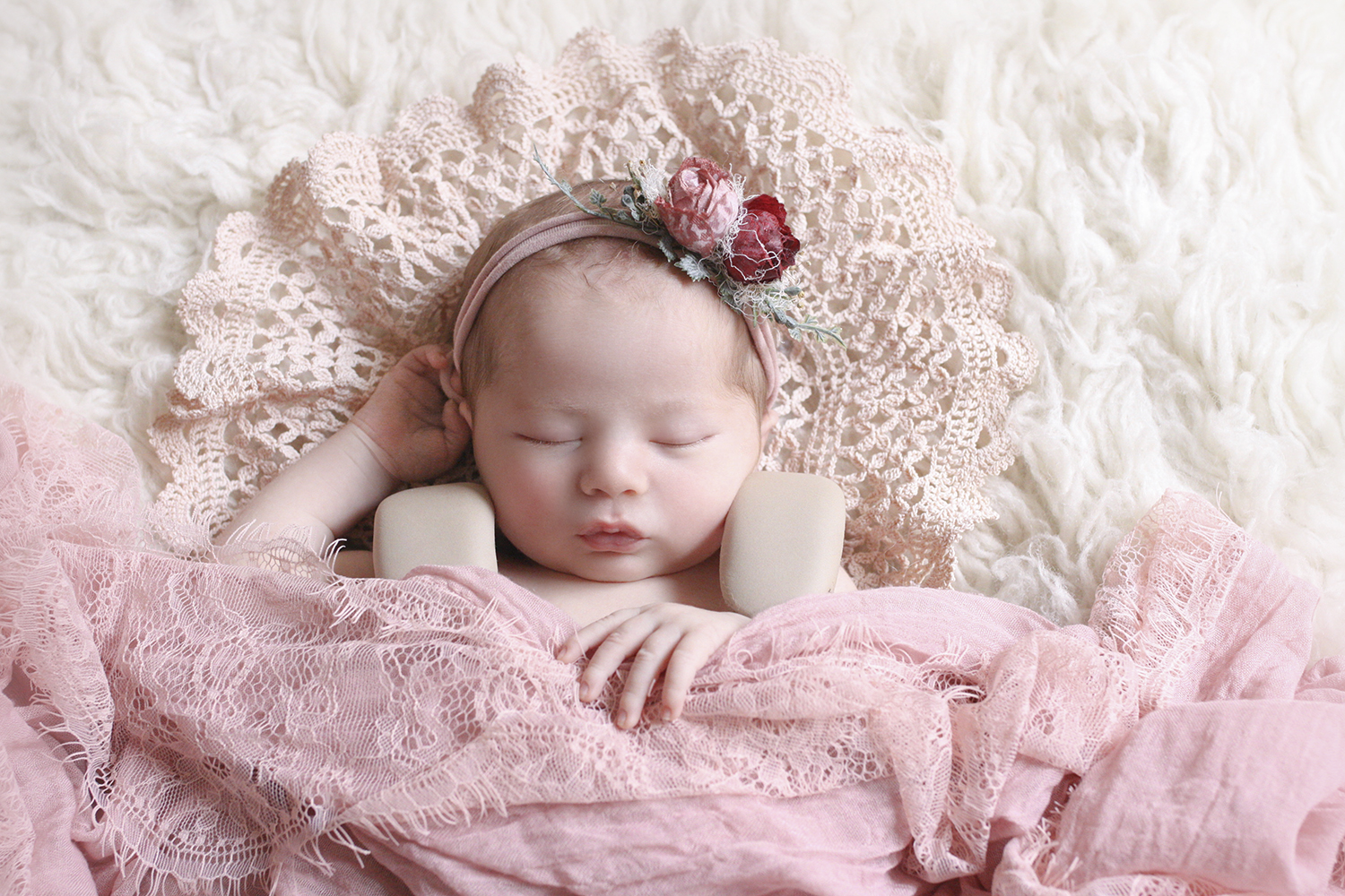Newborn baby girl sleeping on cream fur with pink lace doily and wrap and flower tieback