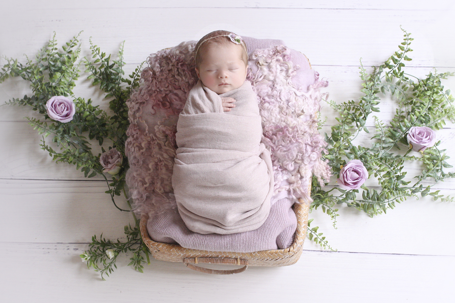 Newborn baby girl sleeping in rectangle cane basket with purple blanket and wrap and curly felt on white wooden floor with vine and purple flowers with purple tieback