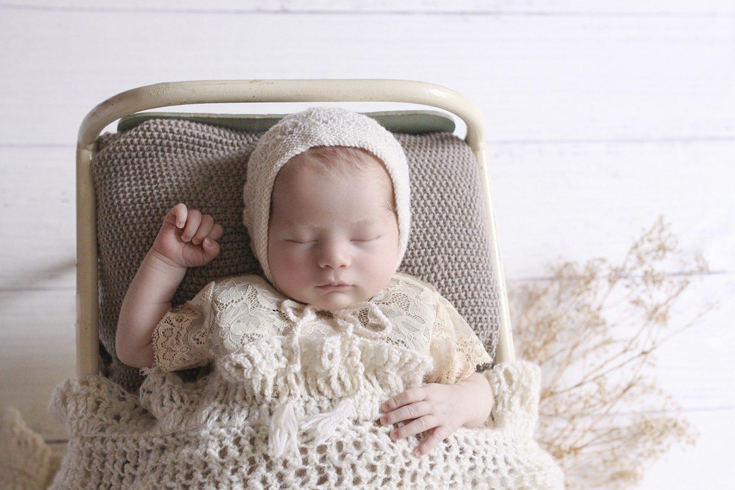 Newborn baby girl sleeping in cream vintage iron bed with brown blanket and cream lace romper and knit wrap and bonnet on white wooden floor