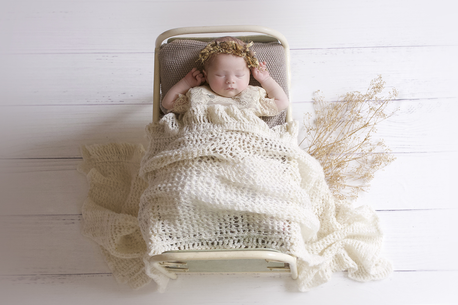 Newborn baby girl sleeping in cream vintage iron bed with brown blanket and cream lace romper and knit wrap and flower tieback on white wooden floor
