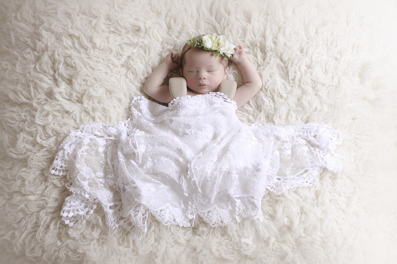 Newborn baby girl sleeping on cream fur with white lace wrap and flower halo