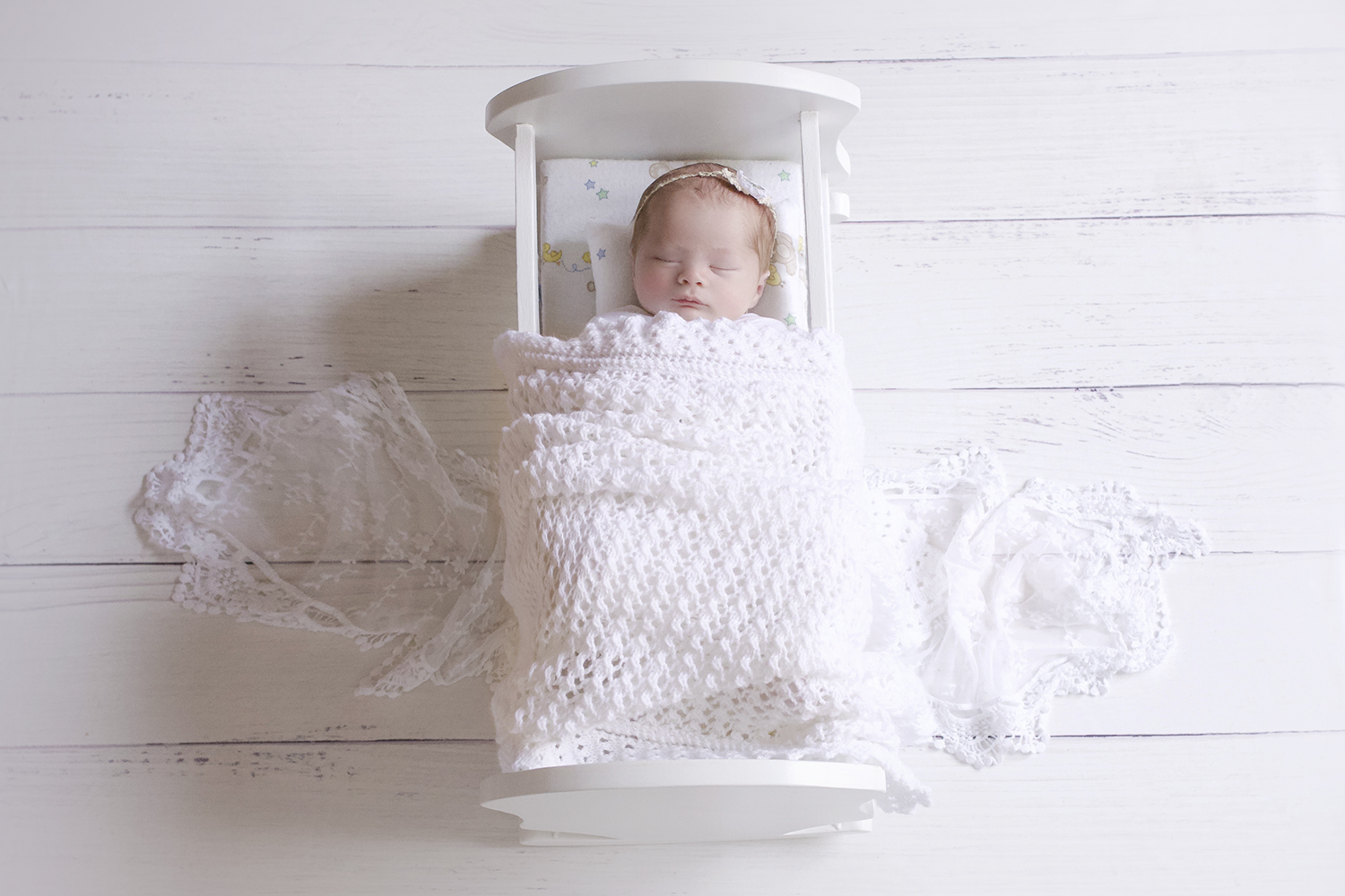 Newborn baby girl sleeping in white wooden vintage doll bed with white knit blanket and wrap and tieback