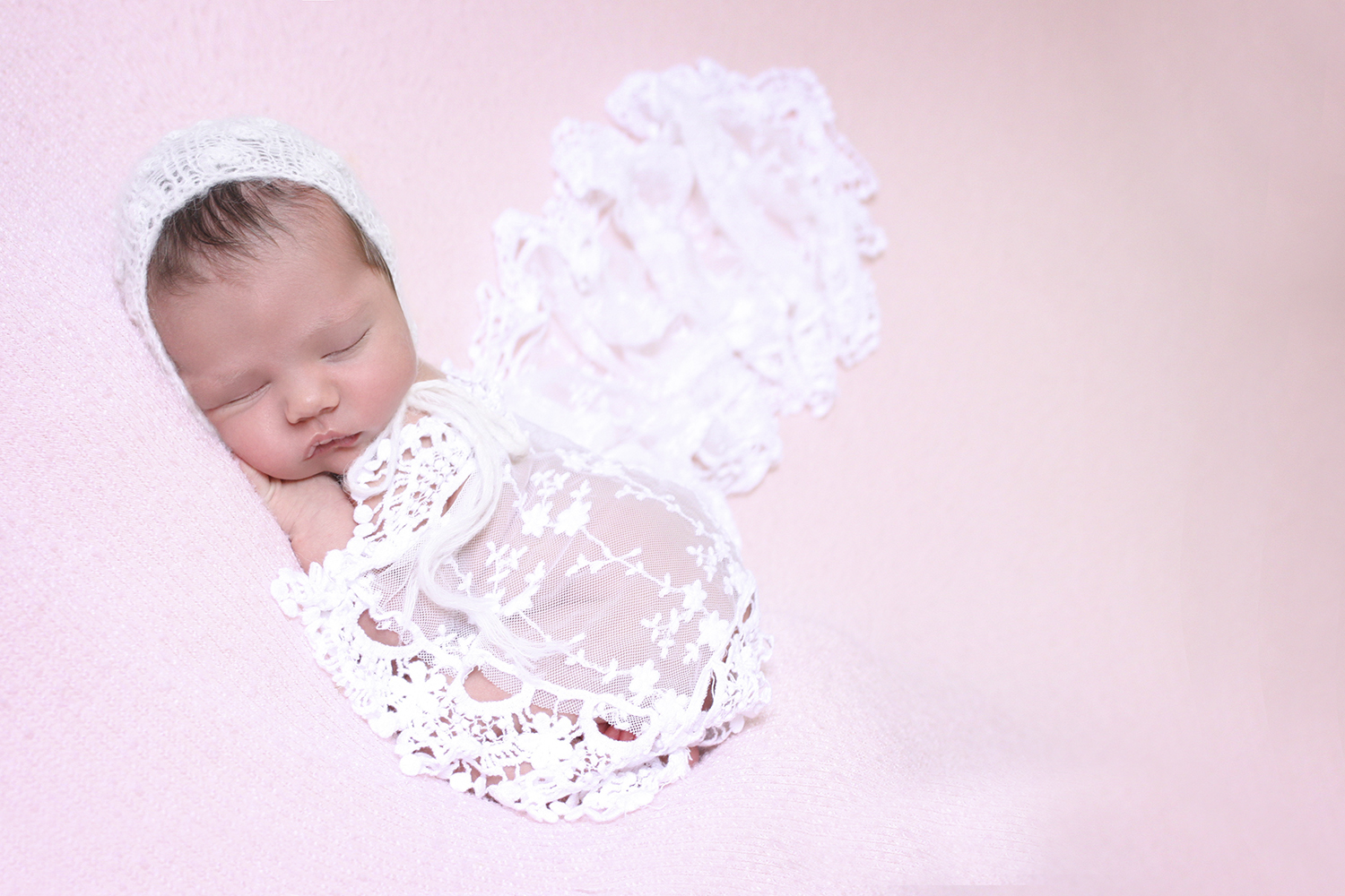 Newborn baby girl sleeping on pink blanket with lace wrap and pink tieback