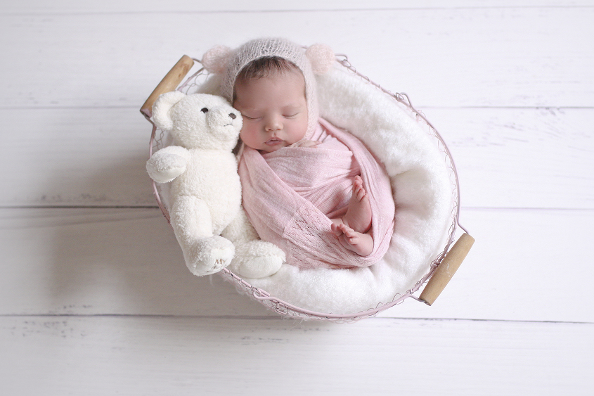 Newborn baby girl sleeping in pink farmers basket with white blanket and pink wrap and pink knit bear bonnet with white teddy on white wooden floor