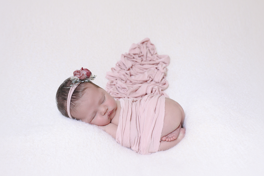 Newborn sleeping on cream blanket with pink wrap and pink flower tieback