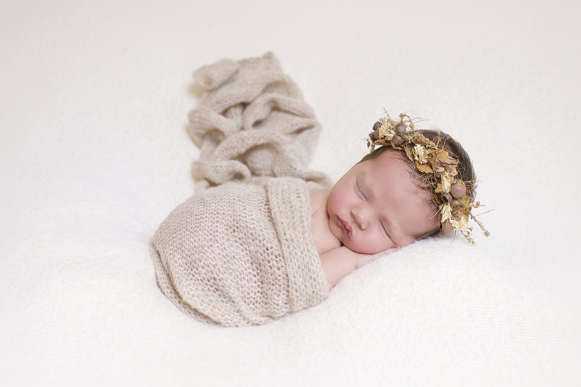 Newborn baby girl sleeping on cream blanket with cream knit layer and brown flower headband