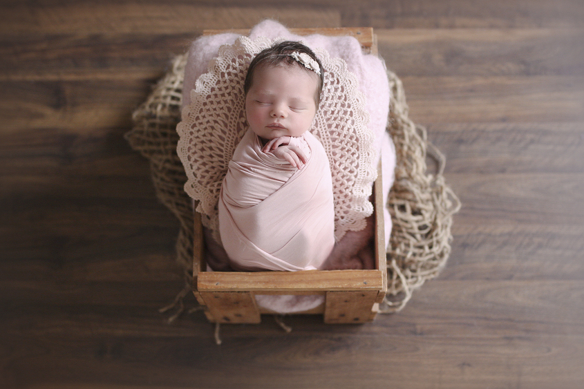 Newborn sleeping in wooden crate with pink wrap and lace doily and blanket and tieback on wooden floor with jute layer