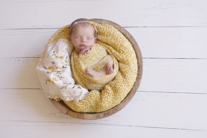 Newborn baby girl sleeping in round wooden bowl with yellow blanket and wrap and tieback and vintage lace doily layer on white wooden floor