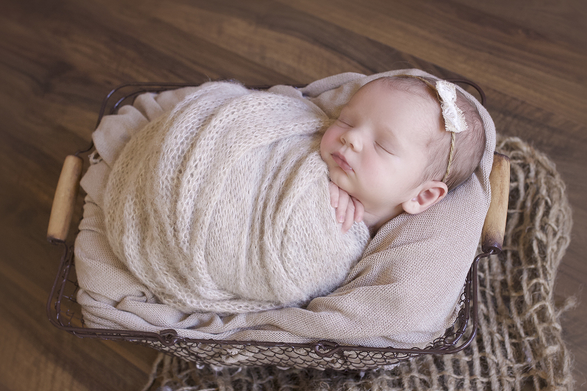 Newborn baby girl sleeping in farmers basket with tan knit wrap and blanket and bow tieback on wooden floor with hessian layer