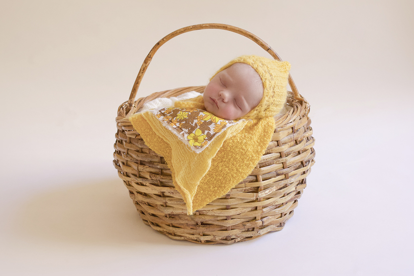 Newborn baby girl sleeping in cane basket with yellow blanket and layer and quilt layer and knit bonnet