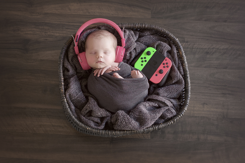 Newborn baby girl sleeping in grey cane basket with grey blanket and wrap wearing pink head phones and pink and green game controller on wooden floor