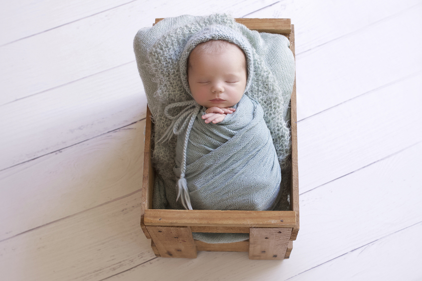 Newborn baby girl sleeping in wooden crate with mint wrap and knit layer and blanket on white wooden floor holding felt heart and wearing knit bonnet