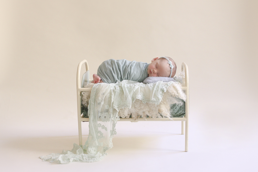 Newborn baby girl sleeping in cream vintage iron bed with green wrap and blanket and lace layer and bow tieback with cream curly felt layer